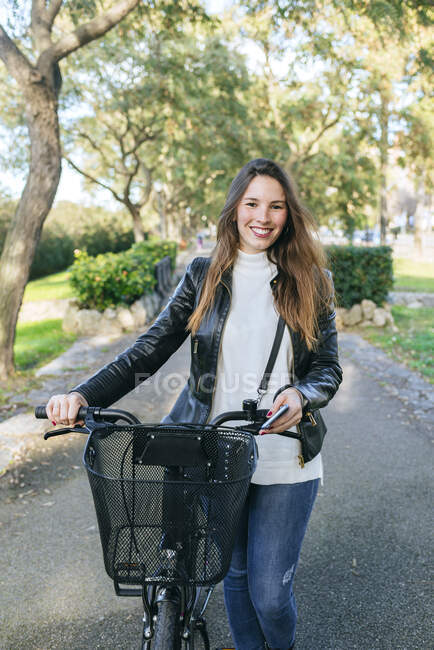 Портрет усмішки молодої жінки з велосипедом у парку. — стокове фото