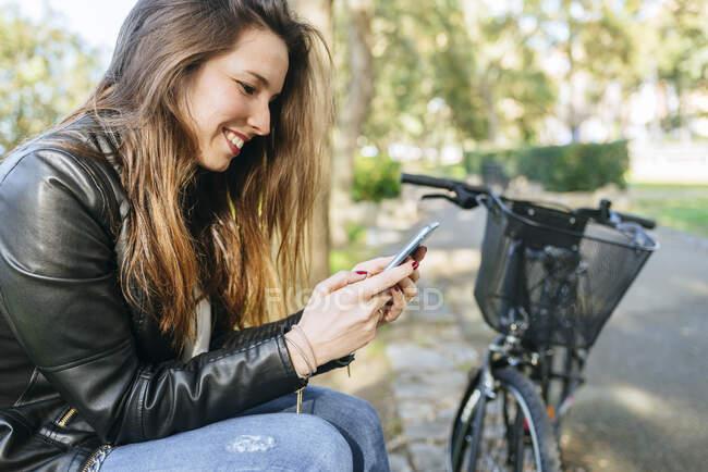 Mujer joven con bicicleta sentada en el parque usando el teléfono celular - foto de stock