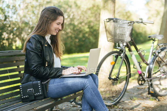 Giovane donna seduta su una panchina nel parco utilizzando il computer portatile — Foto stock