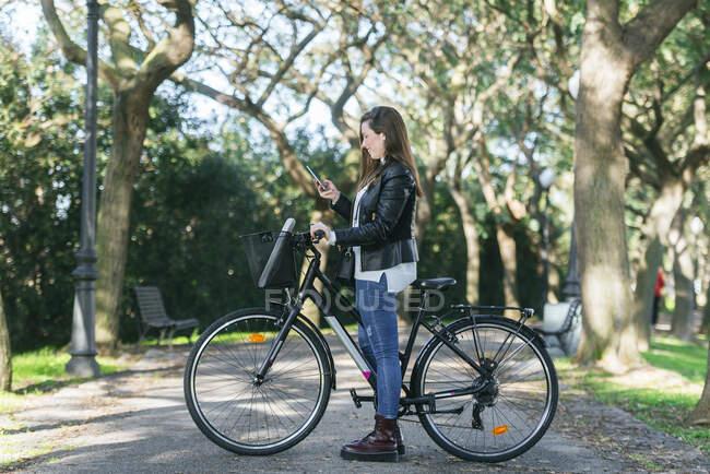 Молода жінка з велосипедом у парку користується мобільним телефоном. — стокове фото