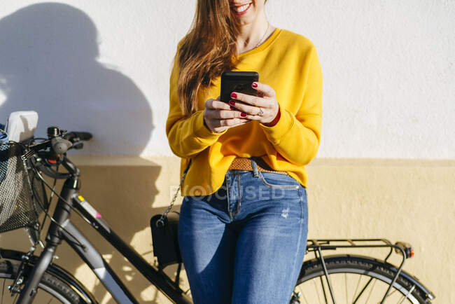 Close-up of young woman with bicycle using cell phone at a wall — Stock Photo
