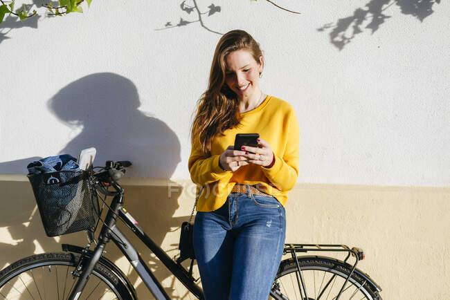 Улыбающаяся молодая женщина на велосипеде с помощью мобильного телефона у стены — стоковое фото