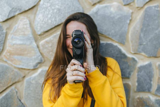 Молода жінка з вінтажною камерою біля кам