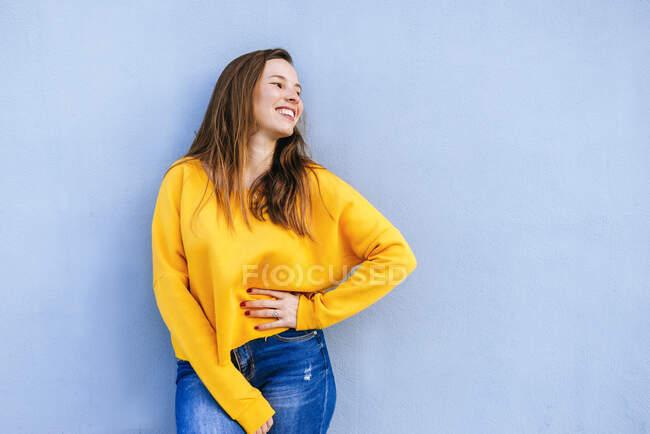 Щаслива молода жінка з жовтим светром стоїть біля блакитної стіни. — стокове фото