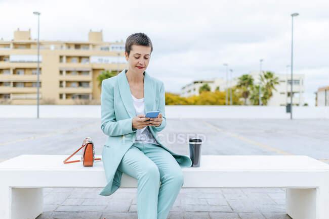 Femme en veste de costume assis sur le banc en utilisant un téléphone mobile — Photo de stock