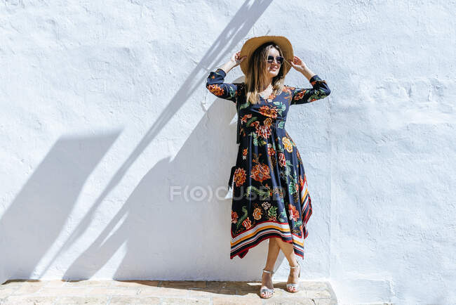 Spain, Cadiz, Vejer de la Frontera, fashionable woman with straw hat standing in front of white wall — Stock Photo