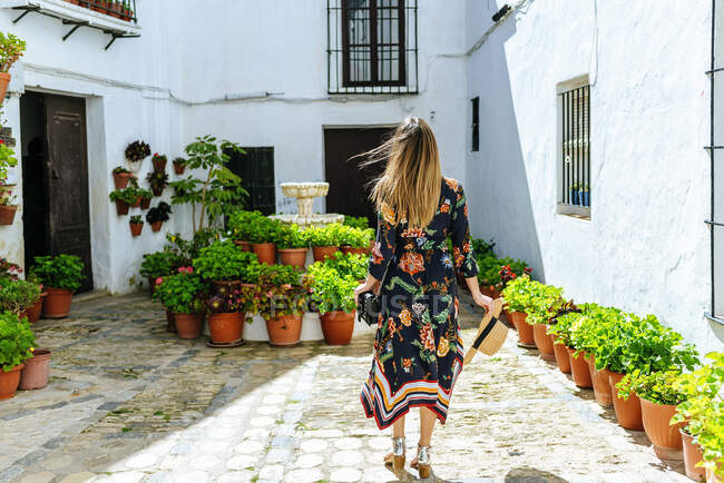 Spain, Cadiz, Vejer de la Frontera, back view of fashionable woman standing at patio — Stock Photo