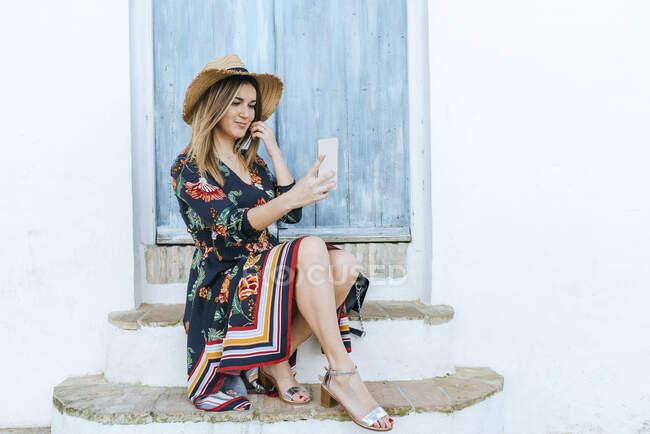 Іспанія, Кадіс, Веєр-де-ла-Фронтера, модна жінка, що робить селфі з мобільним телефоном перед синіми дверима. — стокове фото