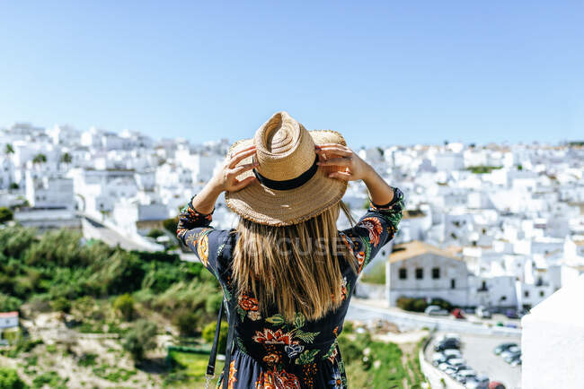 España, Cádiz, Vejer de la Frontera, vista trasera de la mujer con sombrero de paja mirando a la vista - foto de stock
