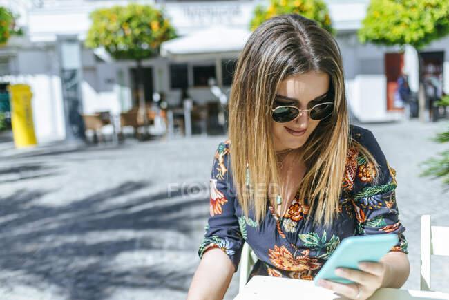 Espagne, Cadix, Vejer de la Frontera, jeune femme assise au café de la rue regardant le téléphone mobile — Photo de stock