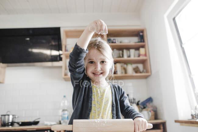 Retrato de la pequeña niña sonriente desplegando la masa en la cocina - foto de stock