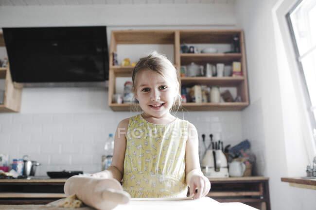Retrato de niña sonriente rodando masa en la cocina - foto de stock