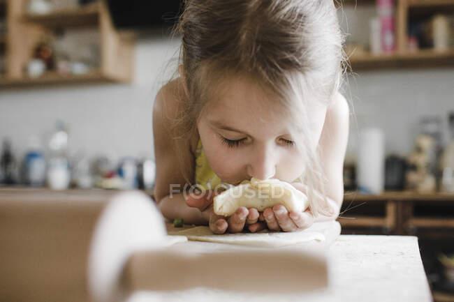 Niña oliendo pasteles rellenos recién preparados - foto de stock