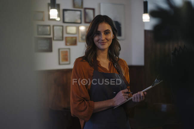 Portrait of smiling woman holding clipboard in restaurant — Stock Photo