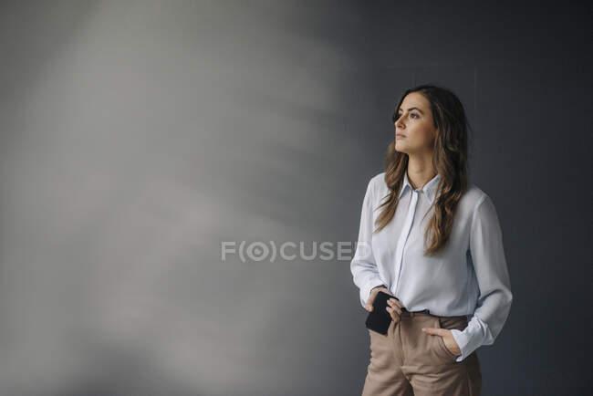 Портрет серьезной молодой предпринимательницы с мобильным телефоном, смотрящей в сторону — стоковое фото