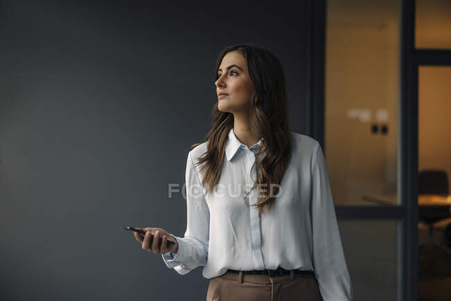 Young businesswoman holding cell phone looking sideways — Stock Photo