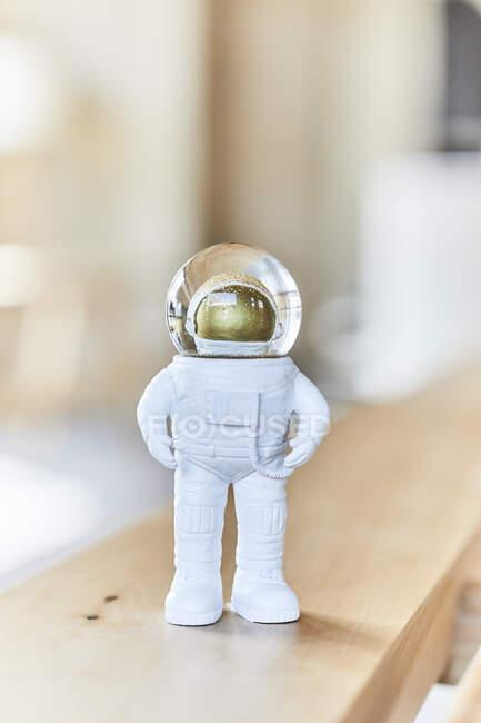 Miniature astronaut figurine on wooden bench — Stock Photo