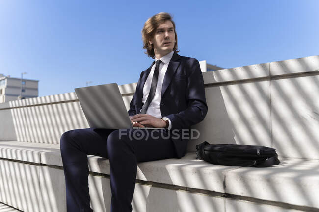 Italy, Florence, young businessman using laptop outdoor — Stock Photo