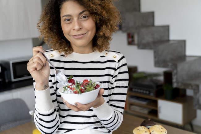 Жінка їсть полуницю вдома. — стокове фото