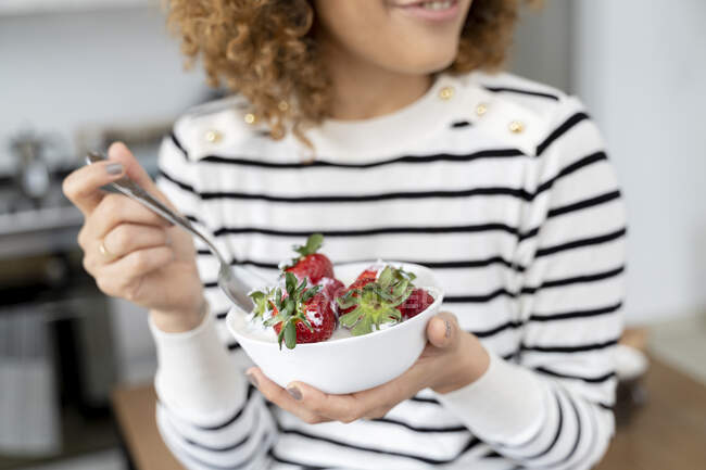 Woman eating strawberries at home — Stock Photo