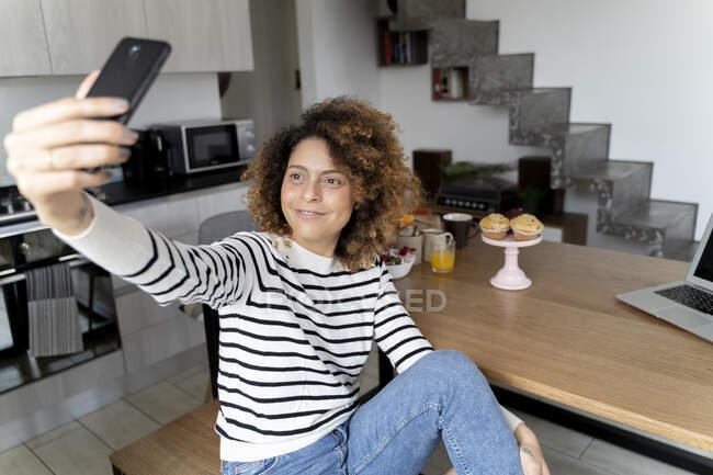 Жінка сидить вдома, користуючись смартфоном. — стокове фото