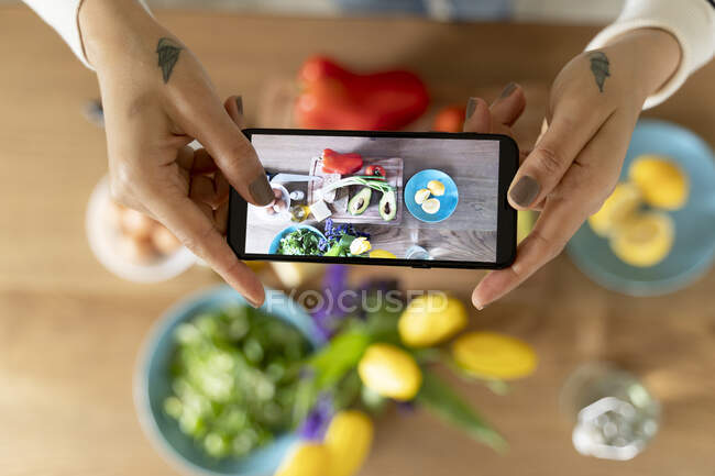 Woman's hands holding smartphone, taking picture of vegetables — Stock Photo