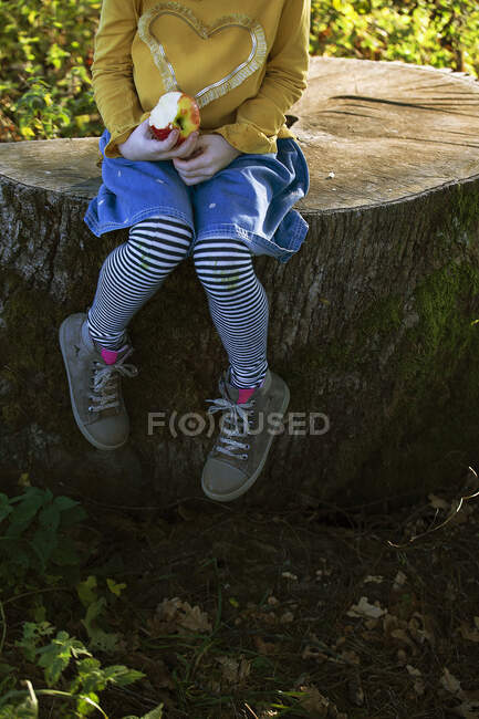 Low section of girl with an apple sitting on a tree stump — Stock Photo