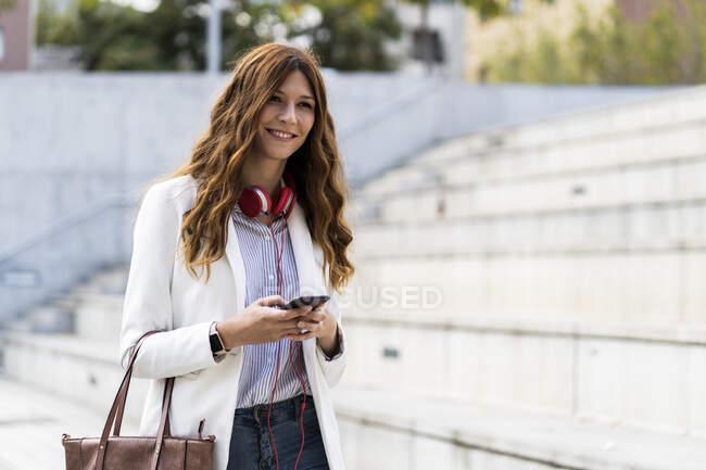 Jeune femme d'affaires qui se déplacent dans la ville, en utilisant un smartphone — Photo de stock