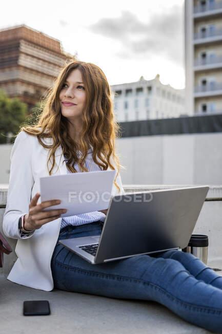 Junge Geschäftsfrau sitzt auf Treppen in der Stadt, arbeitet mit Laptop, hält Dokument in der Hand — Stockfoto