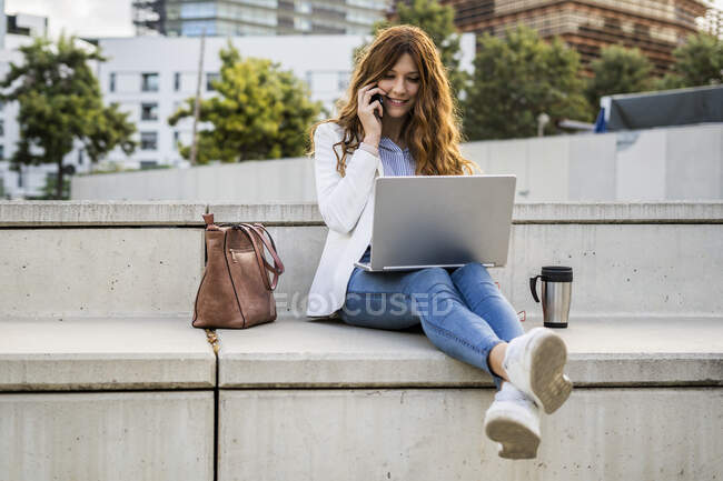 Young businesswoman sitting on bench in the city, using laptop, talking on the phone — Stock Photo