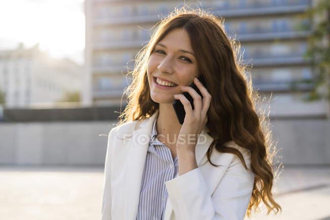 Молода бізнесменка в місті розмовляє по телефону. — стокове фото