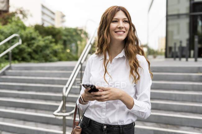Jeune femme d'affaires descendant les escaliers, en utilisant smartphone — Photo de stock