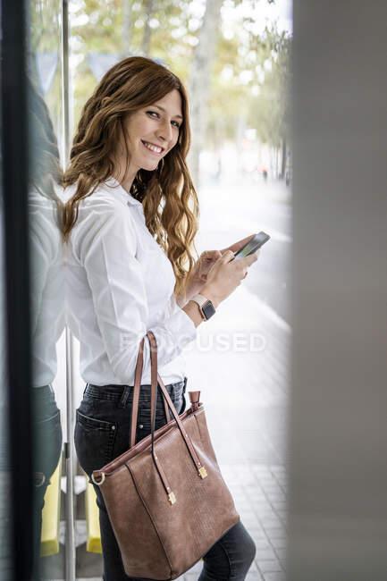 Femme d'affaires en attente à la gare routière, à l'aide d'un smartphone — Photo de stock