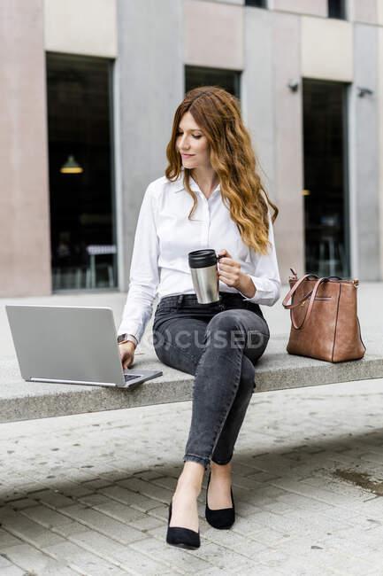 Giovane donna d'affari seduta sulla panchina in città, che lavora con il computer portatile, beve caffè — Foto stock
