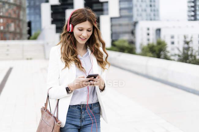 Jeune femme d'affaires qui se déplacent dans la ville, en utilisant un smartphone et un casque — Photo de stock