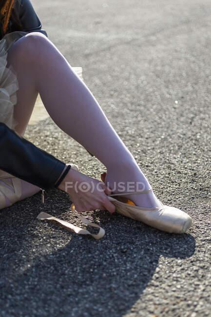 Close-up de mulher sentada colocando em sapatos de balé — Fotografia de Stock