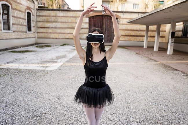 Italy, Verona, Ballerina dancing in the city wearing VR glasses — Stock Photo