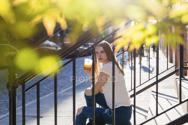 Junge Frau erkundet New York City, sitzt auf der Treppe und trinkt Kaffee — Stockfoto