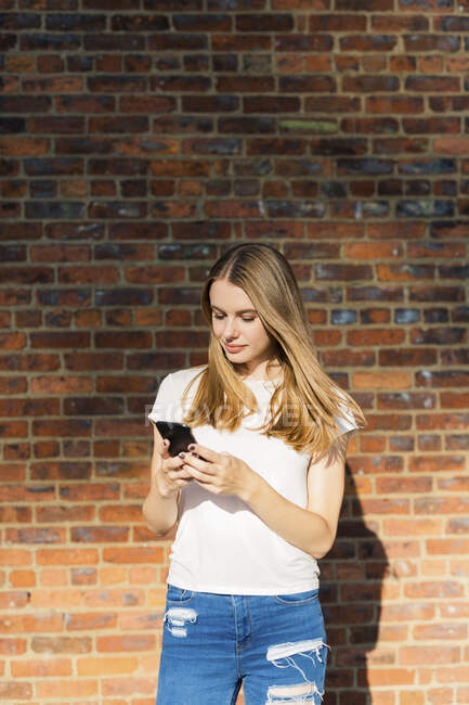 Young woman in front of brick wall, using smartphone — Stock Photo