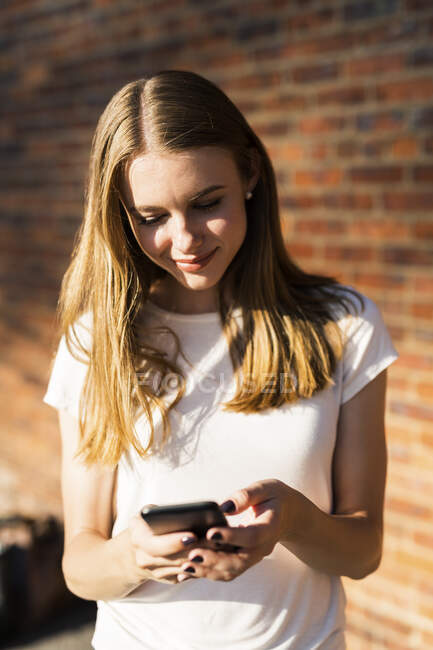 Молода жінка перед цегляною стіною за допомогою смартфона. — стокове фото
