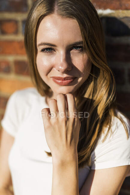 Mujer joven frente a la pared de ladrillo, retrato - foto de stock