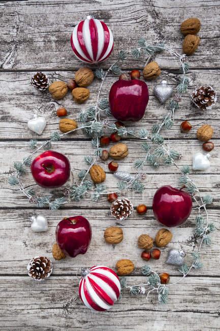 Manzanas de Navidad, nueces, avellanas y decoración navideña en madera - foto de stock