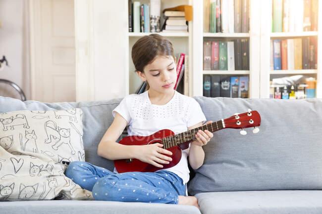 Retrato de niña sentada en el sofá en casa jugando ukelele - foto de stock