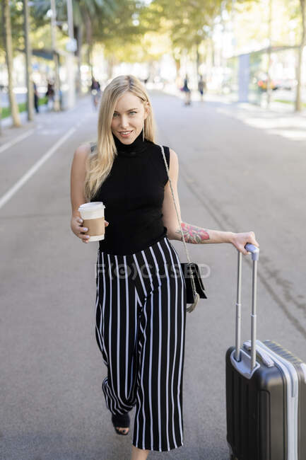 Portrait of smiling blond woman with coffee to go and wheeled luggage walking on street — Stock Photo