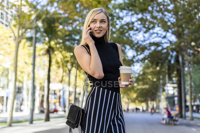Portrait de femme blonde souriante avec café pour aller au téléphone — Photo de stock