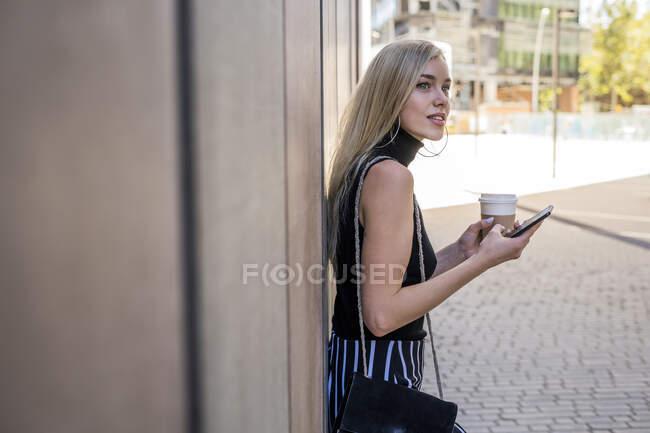 Молодая блондинка с кофе, чтобы пойти и сотовый телефон опирается на стену глядя на расстоянии — стоковое фото