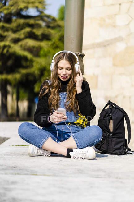 Молодая женщина, использующая смартфон и наушники в Вероне — стоковое фото