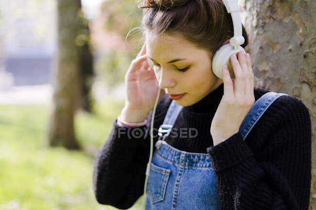 Young woman with headphones in a park — Stock Photo