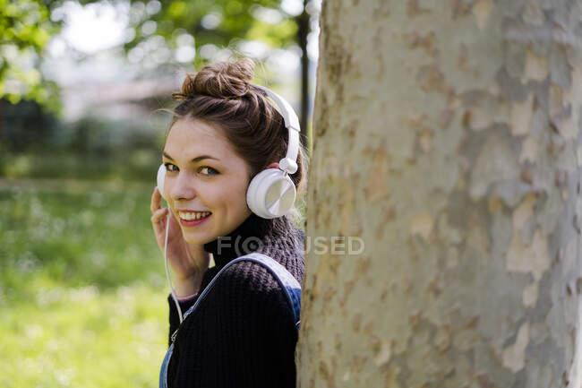 Mujer joven con auriculares en un parque - foto de stock