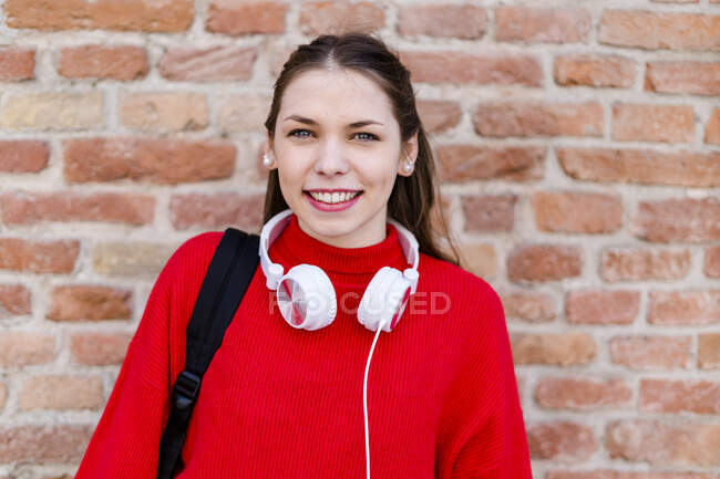 Young woman wearing red pullover, headphones in Verona — Stock Photo